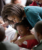 Washington, DC - January 19, 2009 -- Michelle Obama helps a girl at Calvin Coolidge High School where students, military families, and volunteer service groups are working on various projects supporting the troops  in Washington, D.C., U.S., Monday, January 19, 2009.    .Credit: Joshua Roberts - Pool via CNP