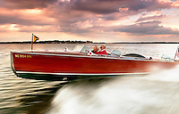 a couple cruise in their classic restored Hackercraft boat along lake Norman in Charlotte, North Carolina.