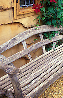 Homemade wooden garden bench against wall with clematis vine 37654