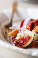 Close up of a bright red sliced fig in a colourful Panzanella, a typical Italian salad served with chunky bread crumbs