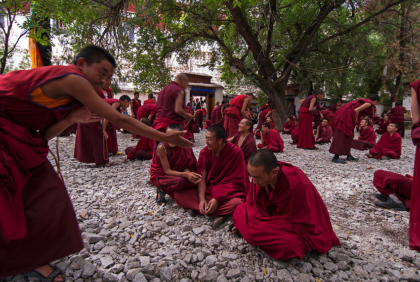 Lhasa Tibet_Sera Monastery is one of the &quot;great three&quot; Gelug university monasteries of Tibet. The monastery was one of the finest locations in Tibet The Bylakuppe Monastery now houses 5,000 Buddhist monks comprising some migrants.<br /> <br /> Debates among monks on the Buddhist doctrines are integral to the learning process in the colleges in the Sera Monastery complex. This facilitates better comprehension of the Buddhist philosophy to attain higher levels of study. <br /> <br /> The debate among monks unfolds in the presence of their teachers. The tradition of such debates is traced to the ancient &lsquo;Hindu Orthodoxy&rsquo; in India and this practice permeated into Buddhist orthodoxy in Tibet in the eighth century. <br /> <br /> Debates are punctuated with vigorous gestures which enliven the ambience of the occasion. Each gesture has a meaning. The debater presents his case with subtlety, robed in a formal monk&rsquo;s attire. Some gestures (said to have symbolic value), made during the debates, generally subtle dramatic gestures are: clapping after each question; holding right hand and stretching left hand forward and striking the left palm with the right palm; clapping hands loudly to stress the power and decisiveness of the defender&rsquo;s arguments denoting his self-assurance; in case of wrong answer presented by the defender, the opponent gestures three circles with his hand around the defenders head followed by loud screaming to unnerve the defender; opponent's mistake is demonstrated by wrapping his upper robe around his waist; loud clapping and intense verbal exchange is common; and the approach is to trap the defender into a wrong line of argument. Each time a new question is asked, the teacher strikes his outstretched left palm with his right palm. When a question is answered correctly, it is acknowledged by the teacher bringing the back of his right hand to his left palm. When the defender wins the debate he makes an allegorical dig at th