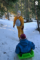 Mother pulling daughter  (7-8)  in sled in forest, French Alps, France (Licence this image exclusively with Getty: http://www.gettyimages.com/detail/82064693 )