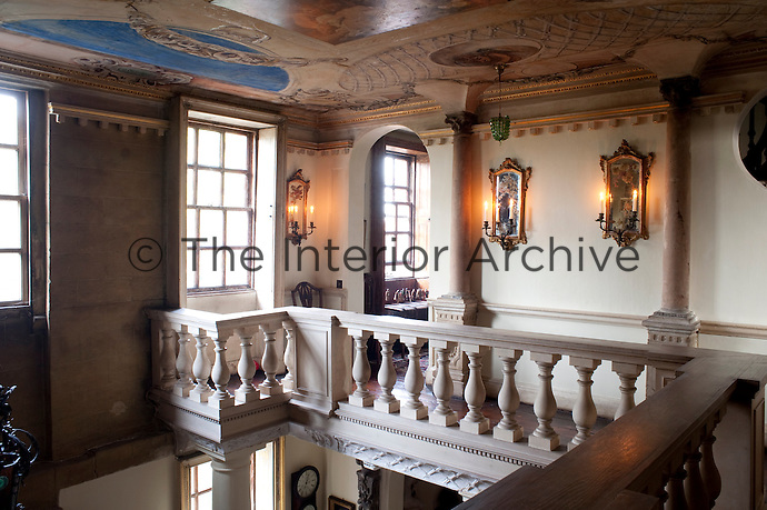 Mirror backed wall sconces illuminate the first floor of the galleried entrance hall