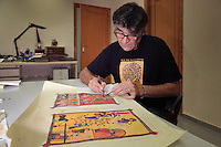 Jose Vicente highlights the gilt painting with golden ink and then age his work with a small scalpel at the printing studio of Scriptorium SL in Valencia, Spain. Picture by Manuel Cohen