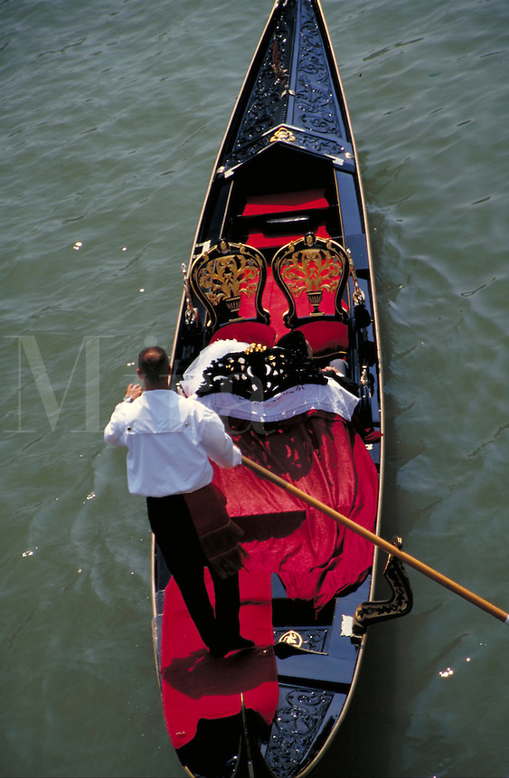 A bride and groom take a gondola ride through Venice, Italy. romance, boat, boats, occupations. Venice, Italy.