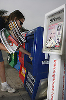 Shelly Gossett of Sun Distributing re-stocks a broken newspaper rack on Garnet Avenue, Pacific Beach in San Diego city, Friday November 16 2007.  A new city-wide ordinance passed by the San Diego City Council will provide more stringent rules for the maintenance and content of the racks found in many parts of the city.  Complaints about the adult-rated content of the materials found inside and the general condition of many of the racks that were not properly maintained by their owners lead to the creation of the new ordinance.  Gossett and her husband David said the owner of this particular rack had been informed of the damage several months ago.
