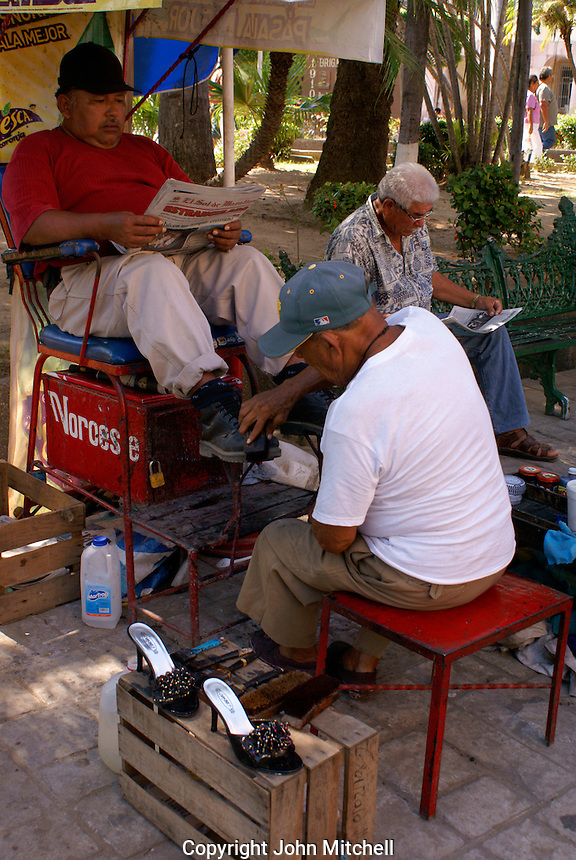 Mexican man reading a newspaper while getting a shoe shine in Old  Mazatlan, Sinaloa, Mexico