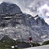 A lone cyclist ascends Grosse Scheidegg, Graübunden, Switzerland. Grosse Scheidegg is a high mountain pass in the Bernese Oberland, connecting Grindelwald and Meiringen. The pass lies between the Schwarzhorn and the Wetterhorn. The road over the pass is open only to bus traffic.