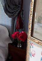 A posy of red garden roses contrasts with the plaid fabric draping the bed