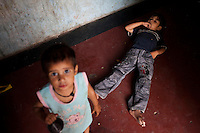 Two of Nafeesa's (unseen, 27) four children in her house in a slum in Tonk, Rajasthan, India, on 19th June 2012. Nafeesa's health deteriorated from bad birth spacing and over-working. While her husband works far from home, she rolls bidis (indian cigarettes) to make an income and support the family. She single-handedly runs the household and this has taken a toll on her health and financial insufficiencies has affected her children's health. Photo by Suzanne Lee for Save The Children UK
