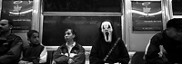 "A subway rider wears a mask from ""Scream"" on Halloween. Subway series shot in New York between the years 1998 and 2001"