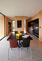 The open plan kitchen/dining area features a Quadritondo table by Roberto Barbieri