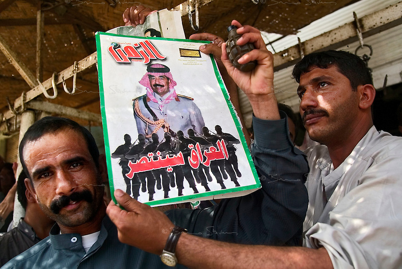 "Fallujah, Iraq, June 10, 2003.Hassan Ali, a shopkeeper, in the souk proudly displays a recruitment poster for ""Saddam Fedayins"", as he does so, another man takes a hand-grenade out of his pocket, and chants ""Down USA"". A large proportion of Fallujah's inhabitants still supports Saddam Hussein, an even larger proportion wishes the US troops would leave for good..."