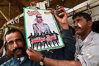 """Fallujah, Iraq, June 10, 2003.Hassan Ali, a shopkeeper, in the souk proudly displays a recruitment poster for """"Saddam Fedayins"""", as he does so, another man takes a hand-grenade out of his pocket, and chants """"Down USA"""". A large proportion of Fallujah's inhabitants still supports Saddam Hussein, an even larger proportion wishes the US troops would leave for good..."""
