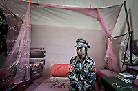 Hka Ra, a KIA cobra soldier, sits at her bed as she waits for her camarades after have finished their training program to the new recruits at the KIA base camp outskirsts of Maiya Jang city, the second largest city under control of the Kachin Independence rebel Army. Since the begining of the Kachin uprising for its sovereignty women always fought by side the rebel soldiers, but officially, the female KIA was founded in 2007, since then, up to 1500 women have joint to the rebel army. The KIA is enhancing its troops number since the ceasefire was broken out by the Burmese army last June 2011.