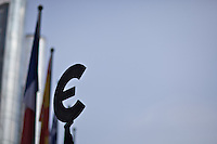 A sculpted Euro currency symbol held aloft with a backdrop of European national flags
