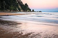 Pastel colours of twilight on golden beach in Totaranui, Abel Tasman National Park, Nelson Region, New Zealand