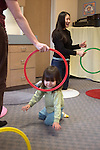 Berkeley CA Asian woman teacher and toddler using plastic rings to experiment with rhythm movements in parent-child, extracurricular music and rhythm class