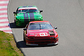 Number 81 a Mazda RX7 in front of a green 1986 Porsche 944 in the G70 Plus race at Circuit Mont-Tremblant, Quebec