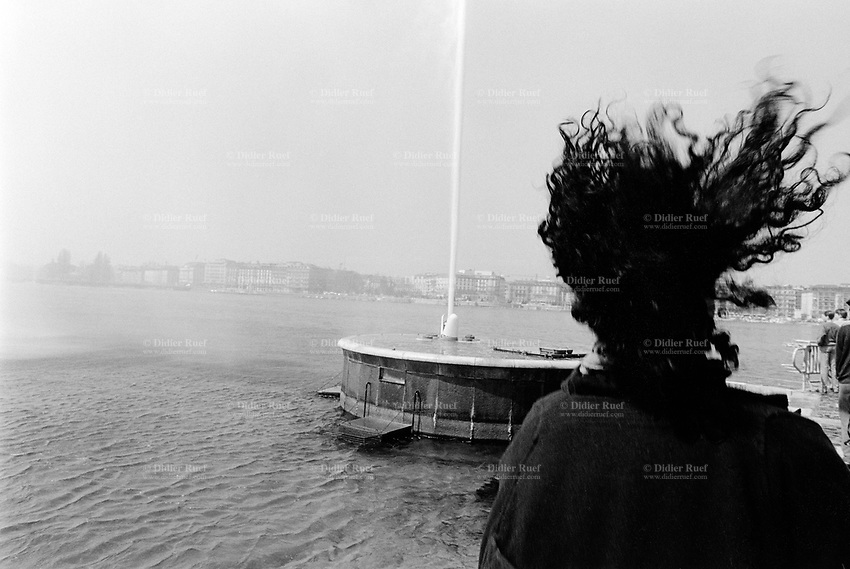 """Switzerland. Geneva. Woman's dark long curly hair blowing in the wind and the famous water fountain """" Jet d'eau """" on the lake of Geneva. © 1988 Didier Ruef"""