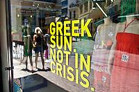 """Atene vetrina di negozio con scritta """"il sole greco non è in crisi"""""""