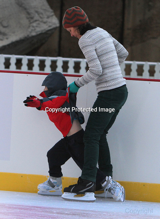 An adult helps this young ice skater around the rink at San Francisco Embarcadero center.