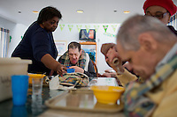 Caregivers help (from left) George Eugene Rouse, Jr., 68, and Randy Russo, eat lunch in the residences in Malone Park at the Fernald Developmental Center in Waltham, Massachusetts, USA.  Ronnie and his twin Randy, 60, both blind and unable to speak, have lived at the Fernald Center for 55 years.  Rouse was born without problems but contracted spinal meningitis and was institutionalized in 1951.