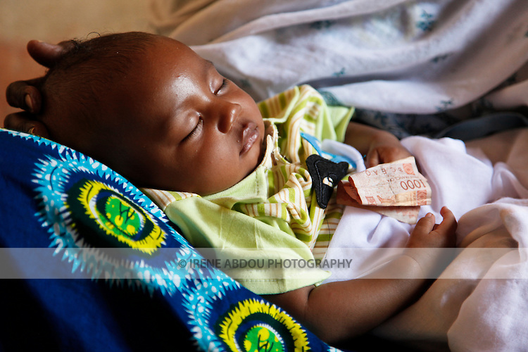 In Ouagadougou, Burkina Faso, a Fulani child sleeps on a woman's lap.  A 1,000 cfa note lies on the child, a gift of a guest at the child's baptism.  While Muslim children in Burkina Faso are normally baptized at age 7 days, this child's family didn't have the money for the celebration until 3 months later.