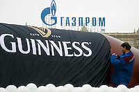 Moscow, Russia, 21/03/2010..A Guinness float is prepared at the 19th annual Moscow St Patrick's Day parade, with a rooftop sign  for Gazprom behind.