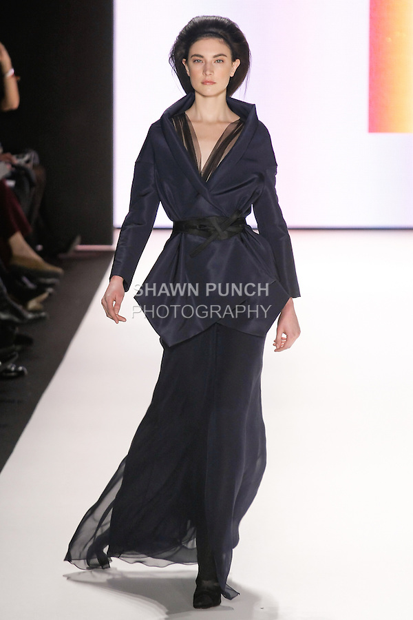 Jacquelyn Jablonski walks runway in a deep navy silk chiffon gown, indigo silk faille peplum jacket, black duchess satin wrap belt, from the Carolina Herrera Fall 2012 collection, during Mercedes-Benz Fashion Week Fall 2012 in New York.