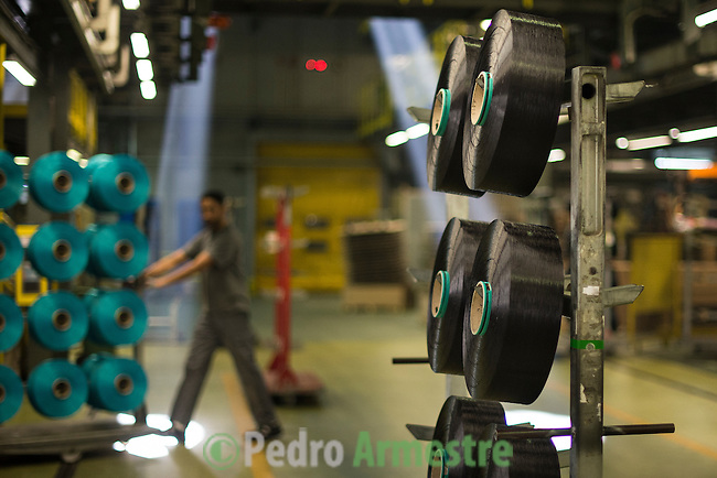 """An employee drives a forklift through the alleyways at a yarn processing plant in Angles, north-eastern Spain on November 6, 2015. Ecoalf, a Spanish Madrid-based firm founded in 2010, has already launched """"a new generation"""" of clothes and accessories made from plastic bottles, old fishing nets and used tires found on land.   © Pedro ARMESTRE"""