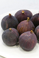 Ficus carica Fig 'Black Mission' dark brown purple fruits, picked and harvested, ripe on plate, showing several more than one