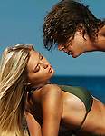 Sensual artistic portrait of a beautiful young couple kissing on the beach in the summer