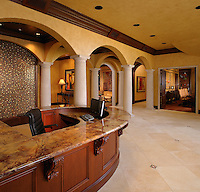 Tuscan style lobby with glass mosaic water wall at the reception desk.