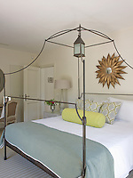 A simple lantern is suspended from the centre of this contemporary wrought-iron bed