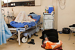 An Iraqi mother sleeps on the floor at the bedside of her daughter, a patient in the cardiac care unit of the Khadamiyah hospital in Baghdad August 25, 2010. After seven years of war, many Iraqi hospitals continue to be overcrowded, in a state of disrepair and stocked with old or outdated medical equipment.   .