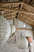 A rustic style living room with a pitched beamed roof and exposed stone walls. Three large paper globe lights hang from the ceiling.