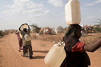Kenya - Dadaab – 21st July 2011. Somali refugees bringing water back to their tents after collecting it from the water tanks inside the camps. The tank had been empty for 3 days.