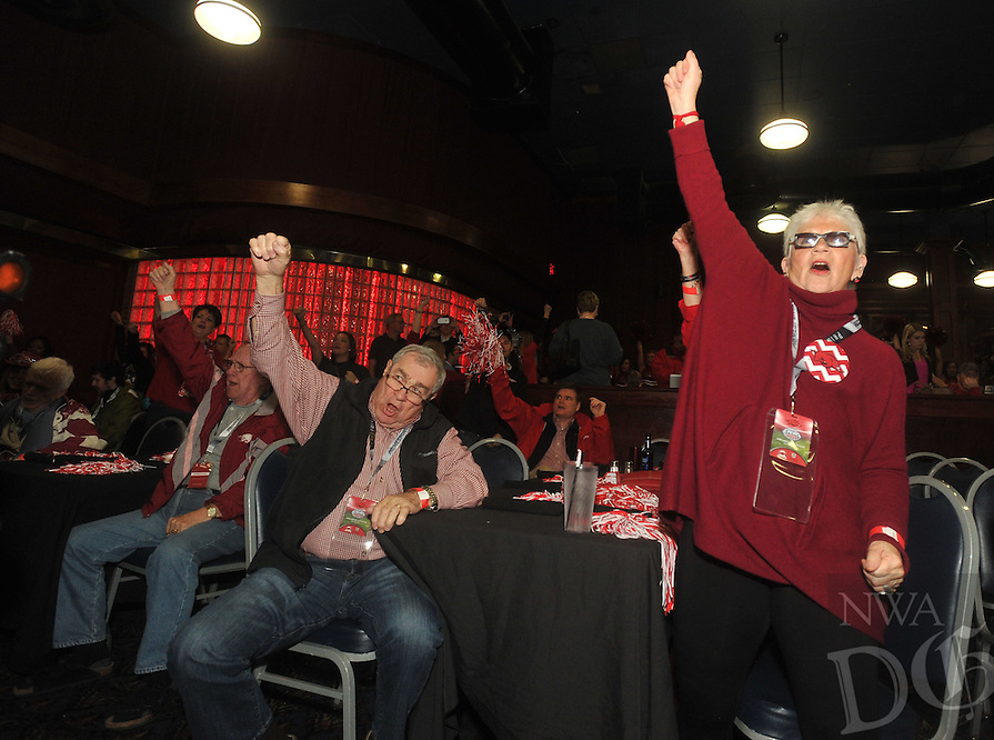 NWA Media/Michael Woods --12/28/2014-- w @NWAMICHAELW...Razorback fans Troy Lefler (left) and Sue Hale call the hogs Sunday night during a pep rally at Dave and Busters in Houston.  The Razorbacks take on the Texas Longhorns in the Texas Bowl Monday night.