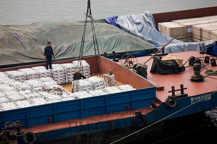 Aluminim ingot blocks being loaded onto cargo ship, Yichang, China