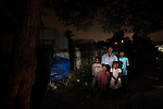 Ronel Metelus, 43, with his children Herby, 12, Hadona, 6, Schneidy 7, Peter 17, in Camp Mina, Port-au-prince, Haiti.<br /> <br /> I came to Port-au-Prince in order to go to school and learn the profession of dressmaker. I used to sell clothes, I would buy a roll of cloth and make it into clothes and I would repair clothes. During the earthquake I was sewing in my house when it started shaking, I didn't know what it was. As it was shaking I grabbed 2 of my little children, 1 under each arm and we ran out. When I got outside I saw people screaming, some rolling on the ground and a lot wounded and bleeding, this is something I will never forget.<br /> <br /> We stayed 20 days living in the streets, after that we moved back in the house but then we couldn't stay any more because it was getting worse and worse with the tremors, so we had to move here to this camp. After the earthquake everyone was afraid to go back in their houses to get some items. We laid bricks on the ground and we put carton on them and then some sheets and we would lie down at nighttime. We sold our cloth to buy food for the children. At the time everything looked desperate, thanks God we were still alive, we didn't die and that means we had to keep living and do the best we can to survive, the situation was very difficult. <br /> <br /> I'm feeling like as if I'm not alive here, if I could leave tomorrow I would. There are many reasons why I'd like to leave the camp, I'm facing a situation that I'm not familiar with here, the way we're living we feel very humiliated, we're living with all kinds of people, like gangsters and robbers. Since we're raising children, to live here where the children are witnessing all kinds of bad actions and violence, this is not good for them so I must do my best to get out of this camp. The people here wish they could leave but the don't have the means to leave. I cannot bring my children up here, it's not normal, I think the longest someone should live in a camp is 