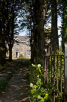 A long shaded driveway lined with tall trees leads to a typical example of an Islay stone-built house