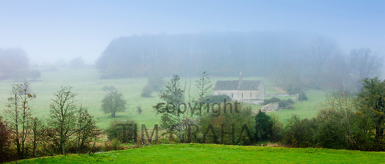 Misty scene and St Oswald's Church, a remote chapel in a field, at Widford near Burford in The Cotswolds, Oxfordshire, UK