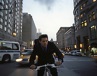 man riding a bicycle in New York City at dusk