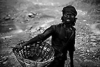 A miner returns to the coal-picker's hamlet on the perimeters of the open-pit coalmines after a long day of work underground in Dhanbad, Jharkhand, India. In the coal-picker's hamlet, every member of the families living there work as coalminers. While the women and children work in the open-pit mines, the boys and men work underground. On 6 September 2006, 54 miners died in a major underground blast at the Bhatdih colliery in the Jharia coalmines. Photo by Suzanne Lee