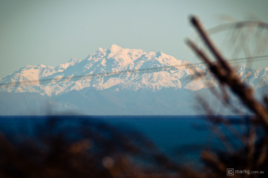 You'll need a good wetsuit to surf during winter in New Zealand - View of the snow capped Kaikoura Ranges on the South Island of New Zealand from the south coast of the Wairarapa.