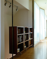 A suspended book shelf also works as a balustrade for the staircase that sweeps down behind it