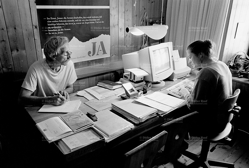 Switzerland. Canton Graubunden. Ftan. Lower Engadine valley. Ursula and Reto Pedotti are both social workers and work half of their time for the institution Pro Senectute. On the wall, a poster which says Yes (Ja). The other half, they are are farmers. Swiss alpine farmers. Alps mountains peasants.  © 1997 Didier Ruef
