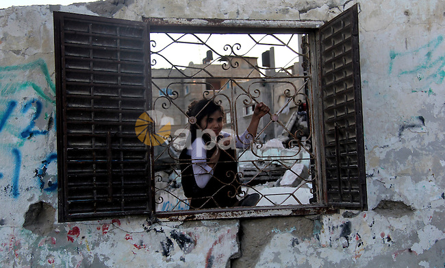 A Palestinian girl looks through a damaged window from his family house which destroyed during the 50-day war between Israel and Hamas militants in the summer of 2014, in the Gaza Strip town of Beit Hanun on April 25, 2015. Photo by Nidal Alwaheidi