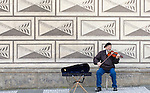 An elderly violinist plays in front of the  Schwarzenberský Palác on the Hrad?anské Nam in Prague.